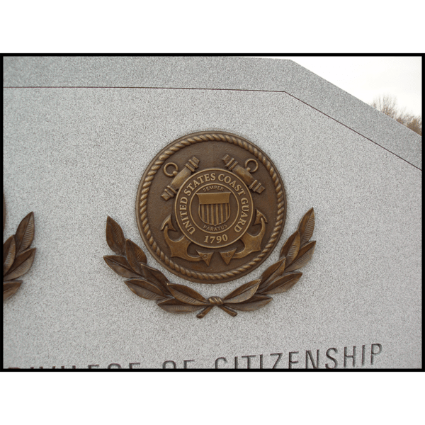 photo closeup of bronze sculpture of military seal on granite monument
