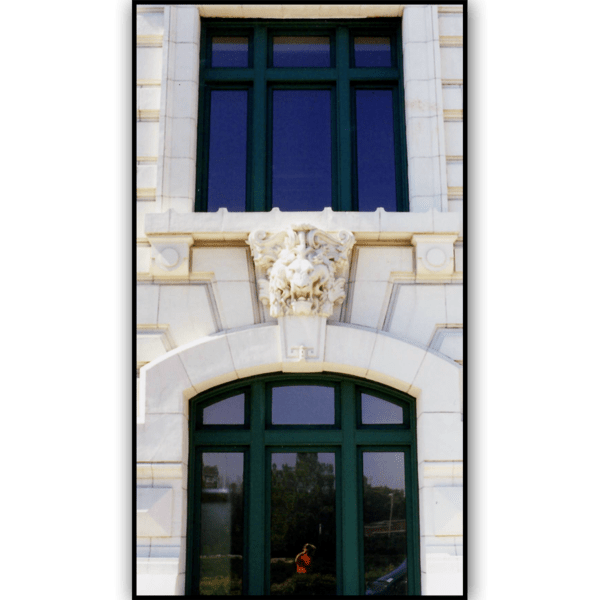 photo of ornament above window on white building with two towers