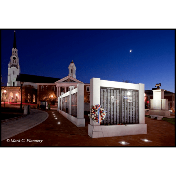 photo of black and gray granite monument in form of a wall on brick hardscaping in city green with buildings and trees behind at night