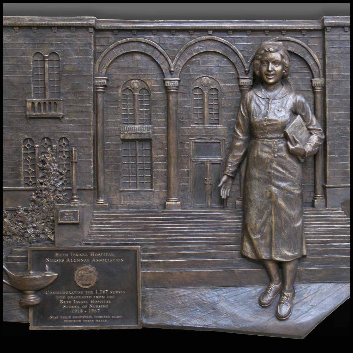photo of bronze-colored relief plaque of female nurse walking outside hospital building
