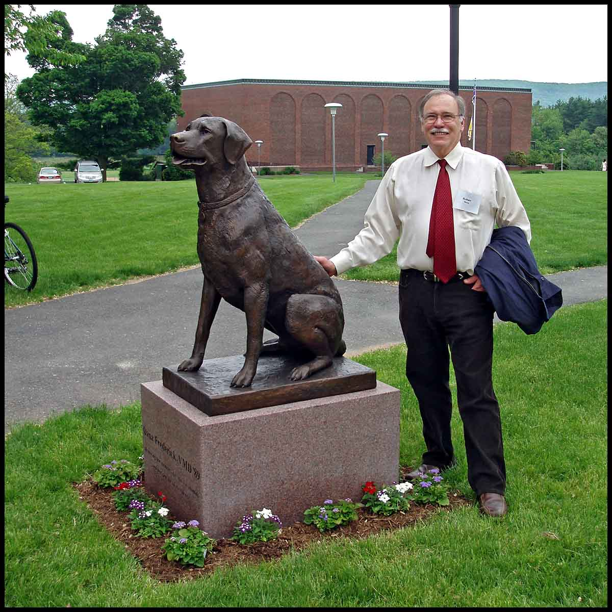photo of bronze-colored sculpture of black labrador on stone base on landscaped campus with sculptor Robert Shure beside it