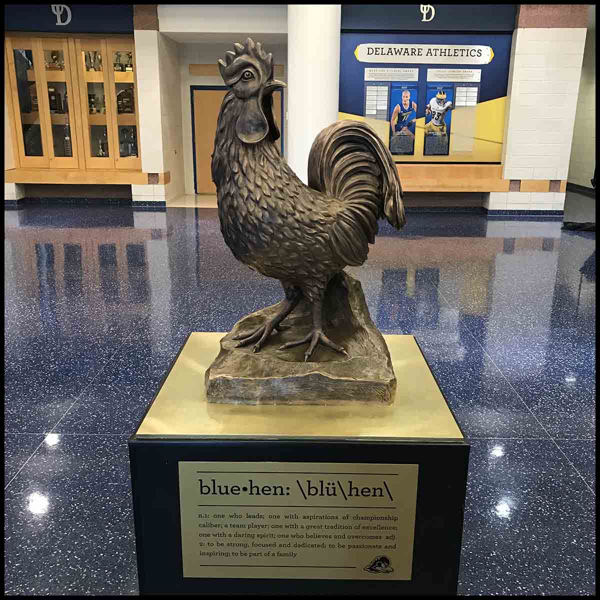 photo of bronze sculpture of hen on black and gold base in large room with blue floor