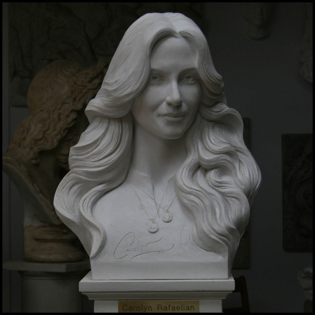 photo of white-colored sculpture bust of Carolyn Rafaelian on white square base with small gold-colored plaque against a black background