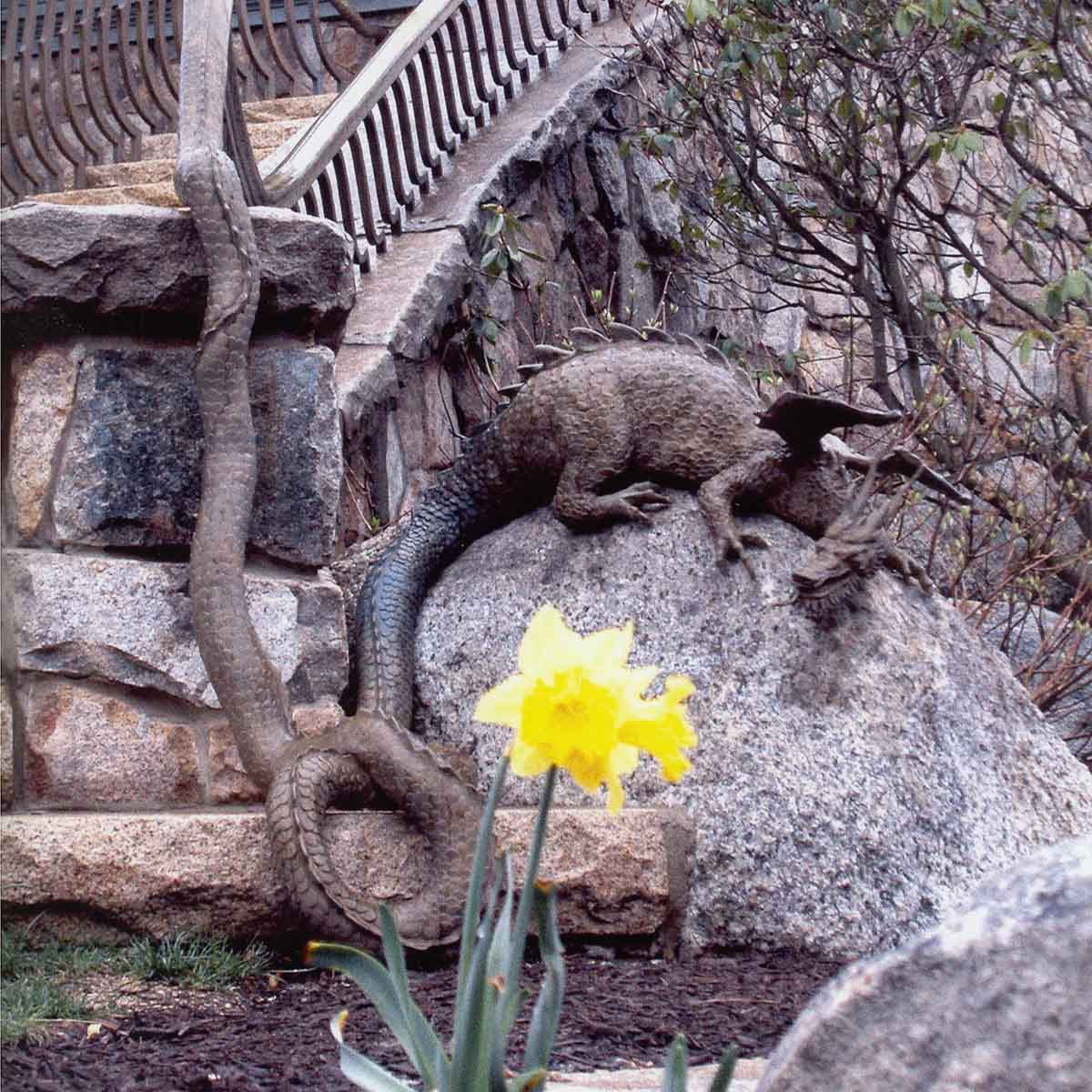 photo of building with stone staircase with a bronze dragon perched on a rock at the bottom