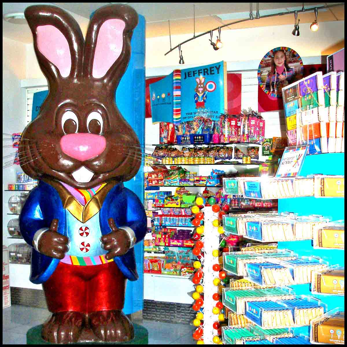 photo of large sculpture meant to look like a chocolate bunny wearing a blue suitcoat and red pants in a candy store