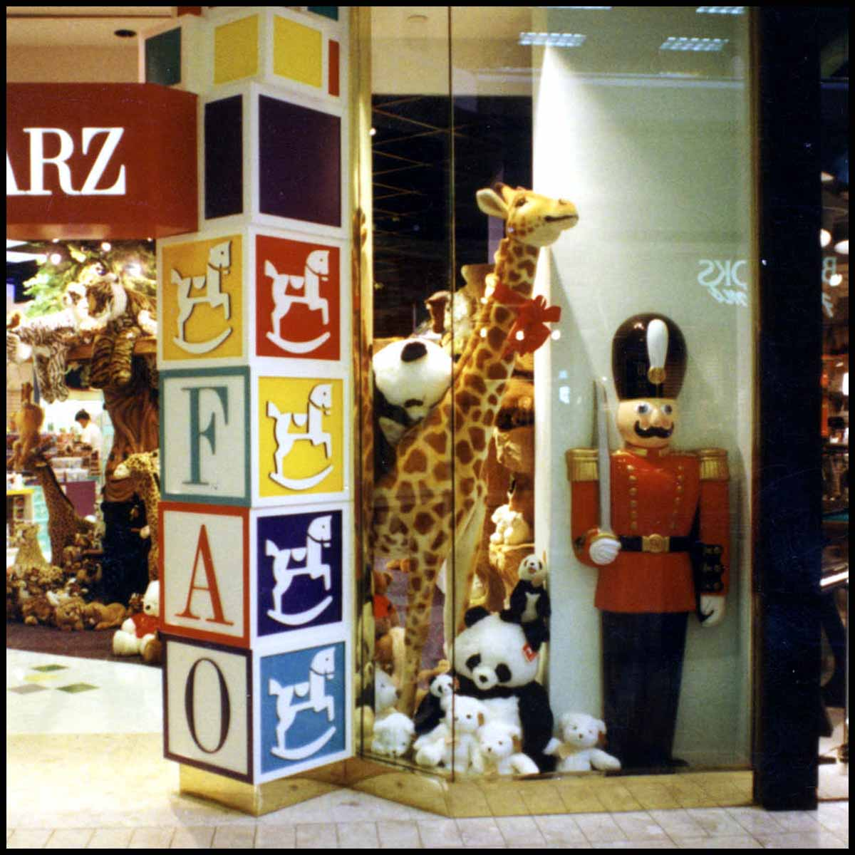 photo of FAO Schwarz toy store front window with logo tower of blocks, stuffed animals, and polychromed toy soldier sculpture
