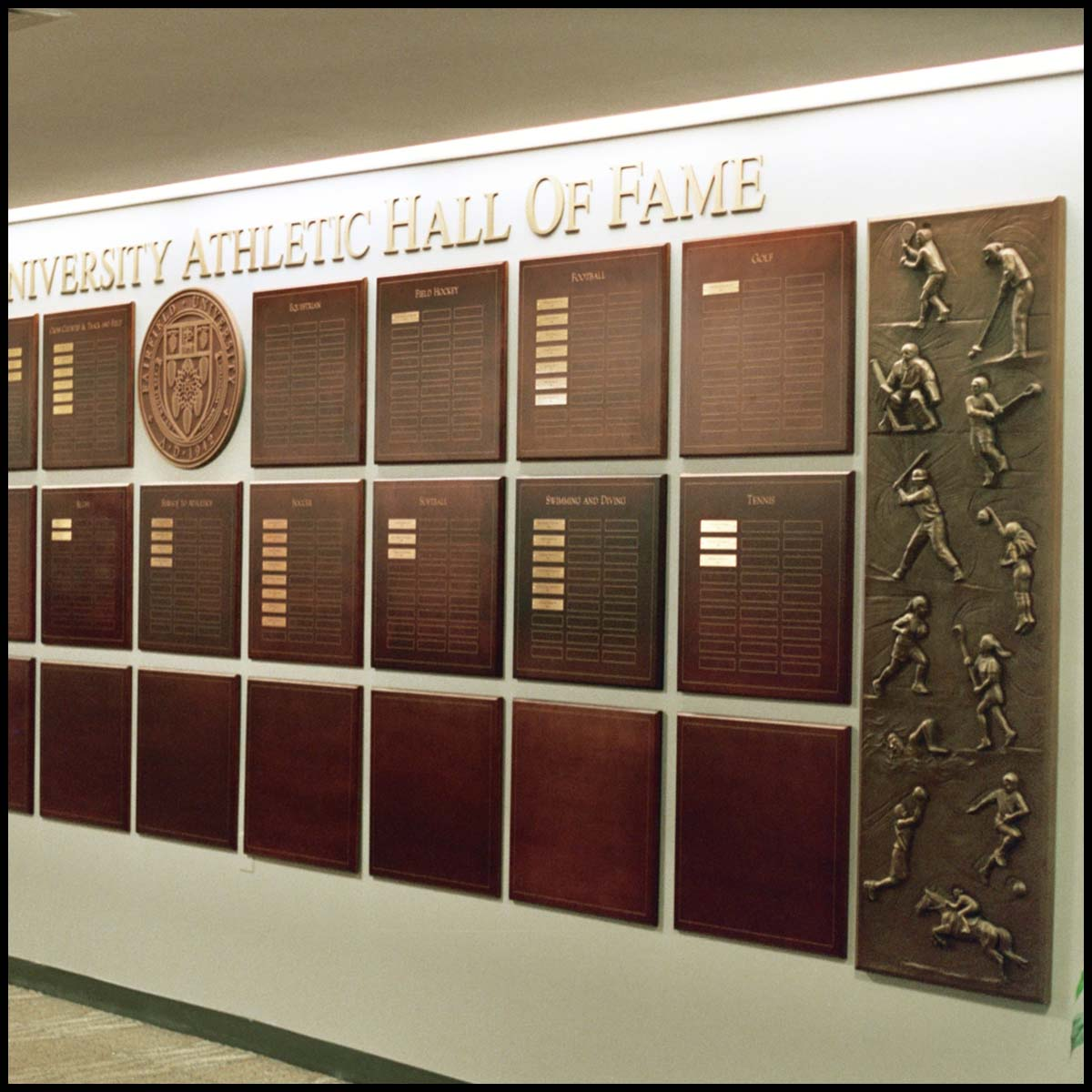 photo of white interior wall with rows of bronze-colored plaques with names on small gold-colored plaques with large bronze-colored relief of various athletes