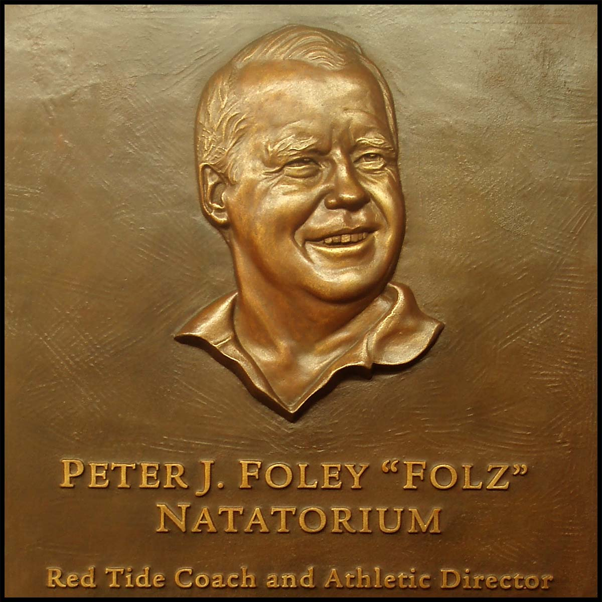 photo of bronze plaque with relief sculpture of Peter Foley on tiled wall