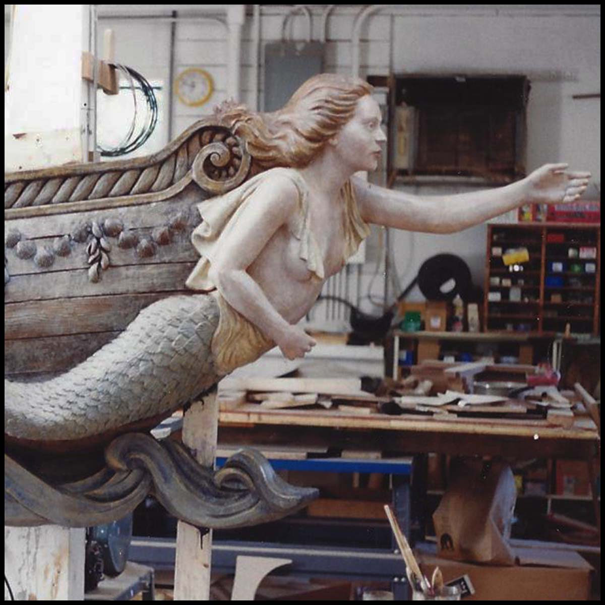 closeup photo of polychromed sculpture of mermaid masthead on ship bow in sculptor's studio