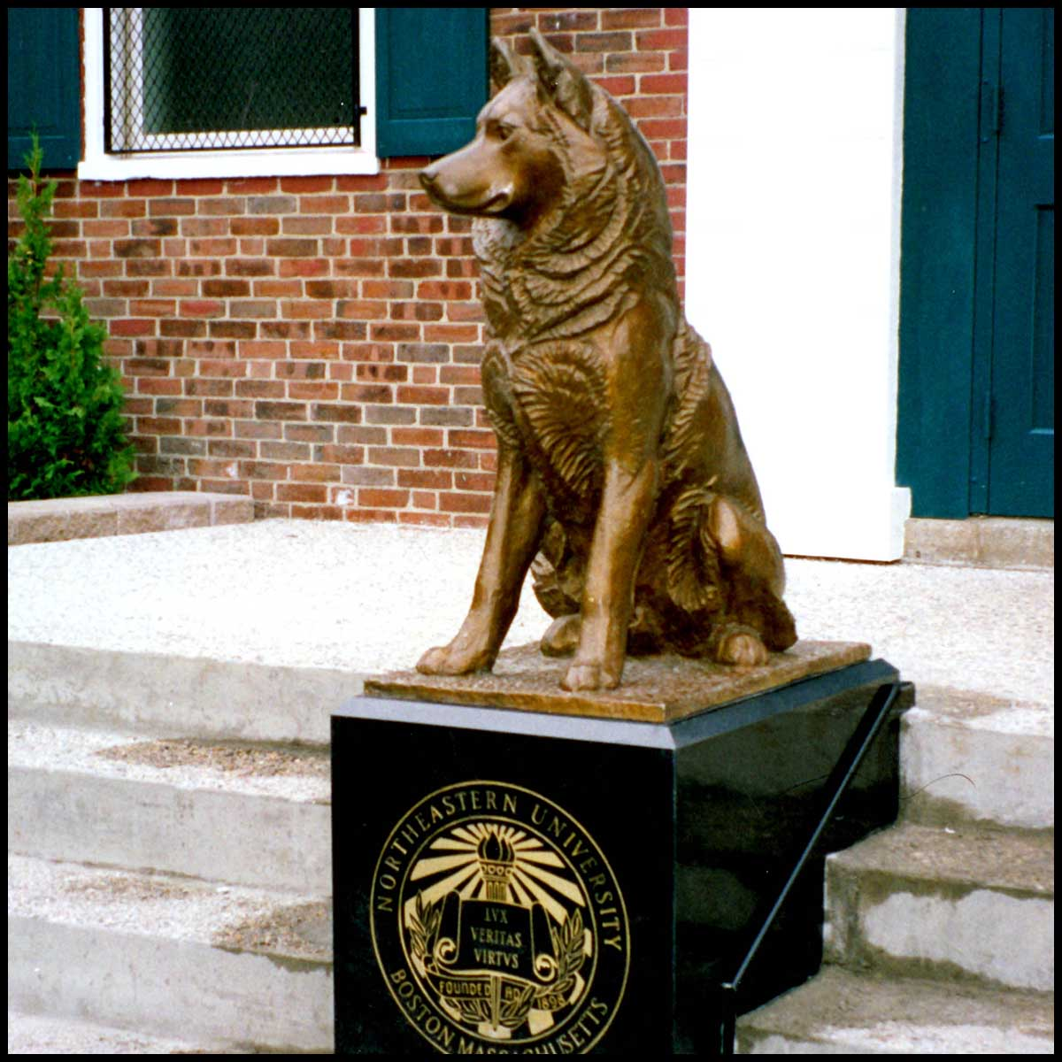 photo of bronze-colored sculpture of seated husky on black base with school logo on staircase