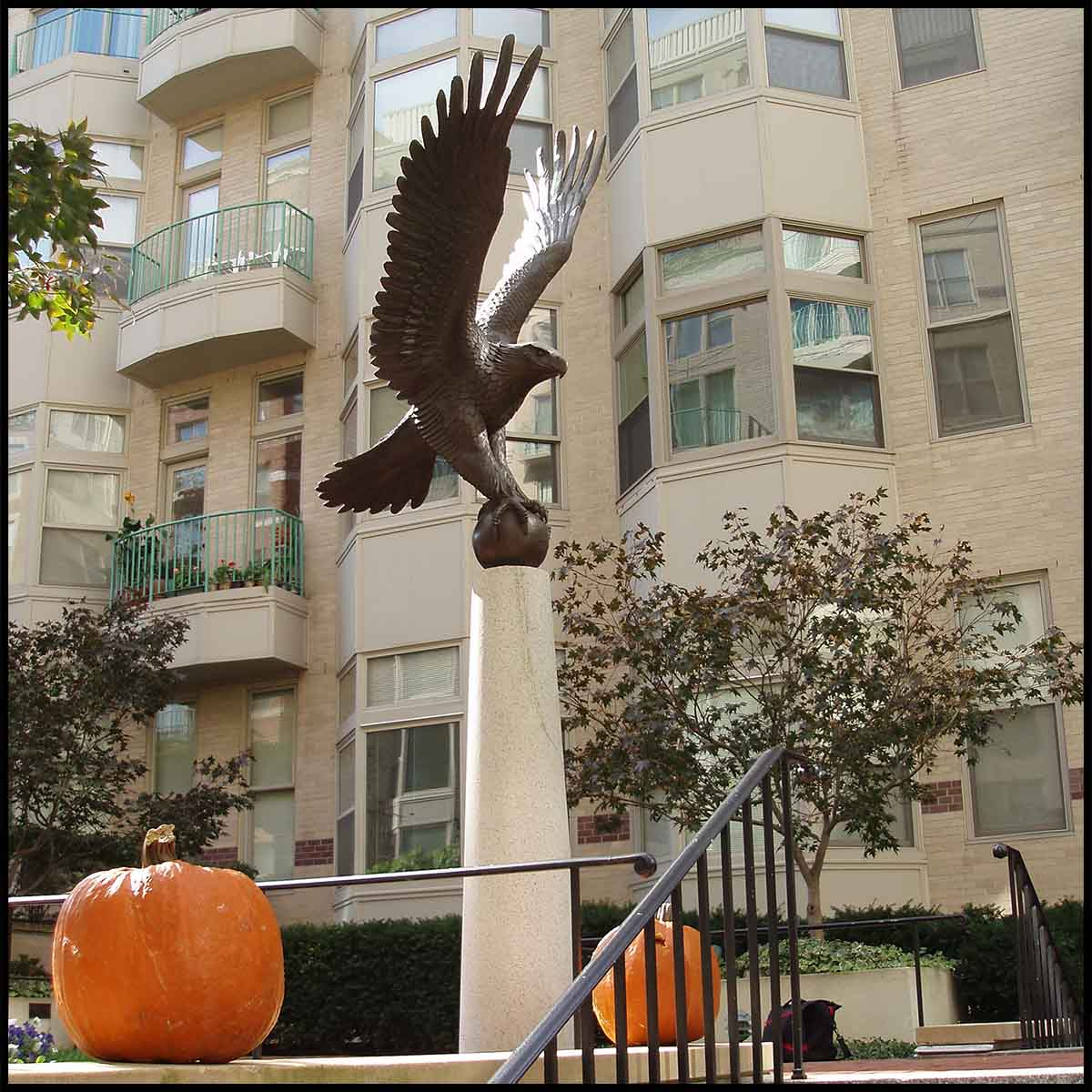 photo of bronze sculpture of eagle perched on ball with open wings atop tall pedestal at the top of a staircase with two pumpkins in front of an off-white building and pumpkins