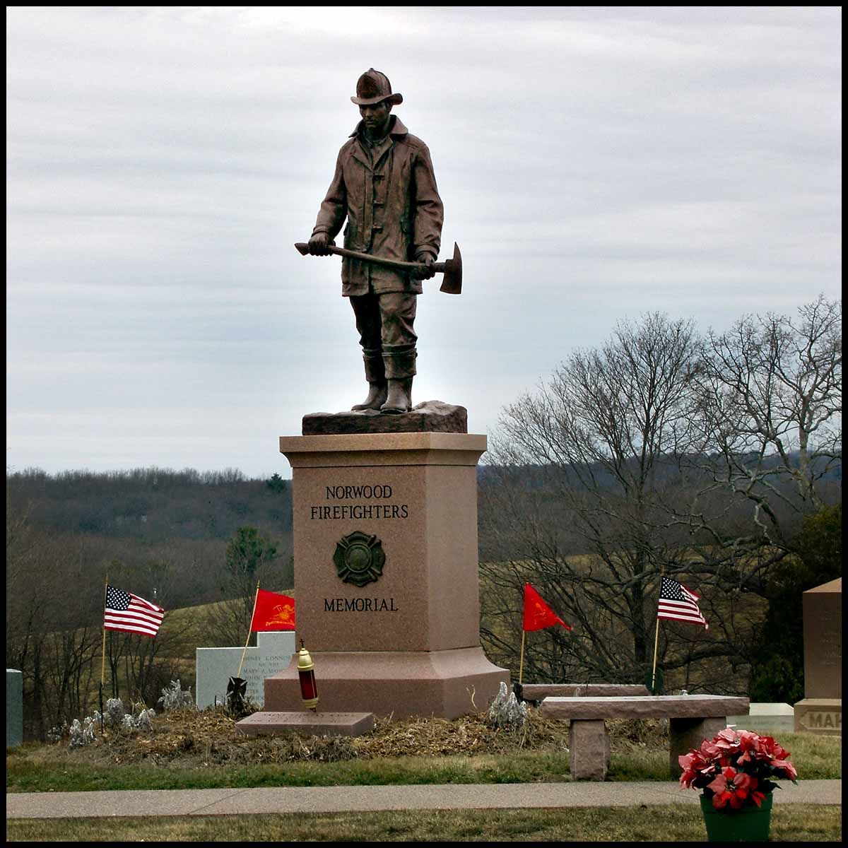 photo of bronze statue of standing firefighter holding an ax atop a tall stone base in a cemetery