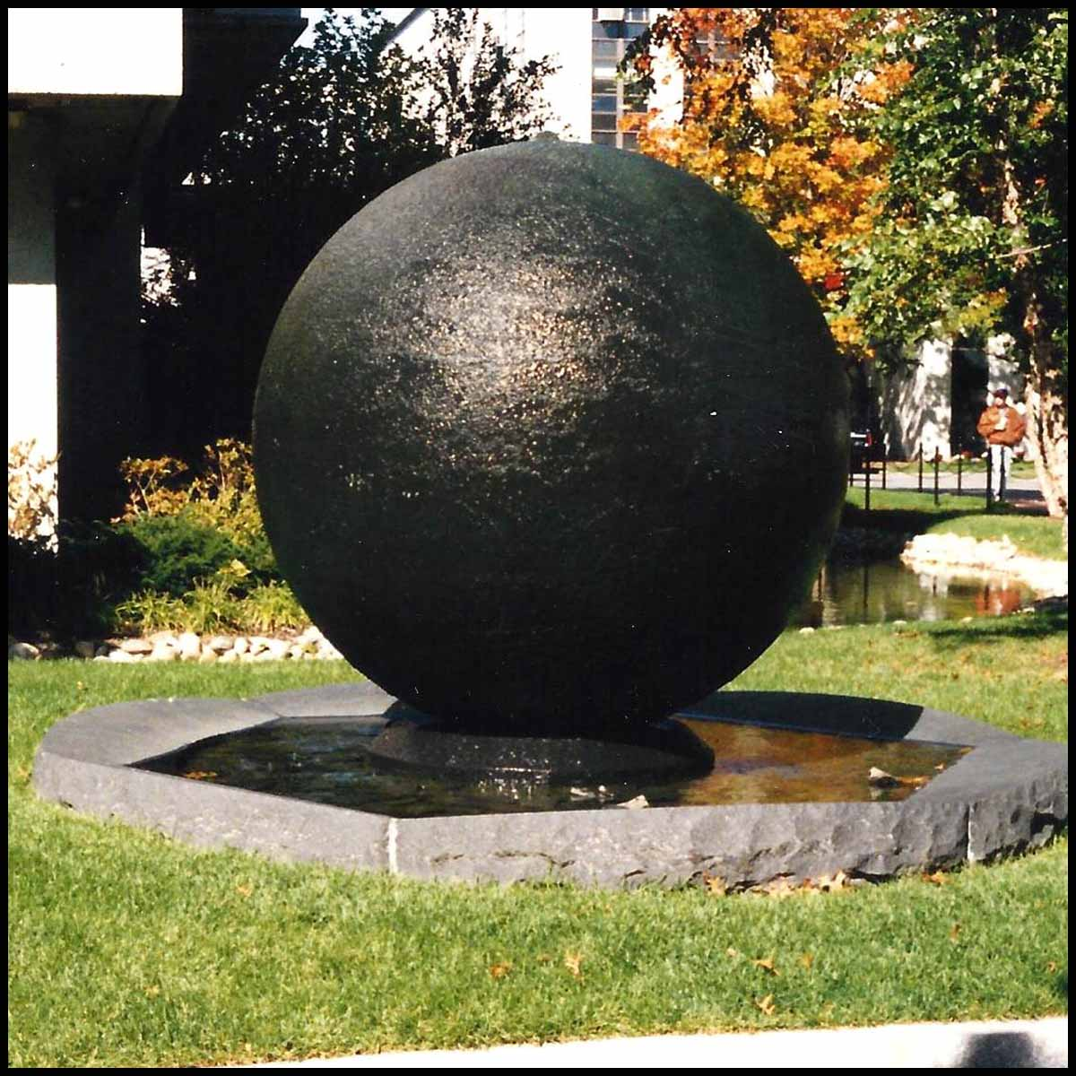 photo of black-colored sphere in stone-rimmed pool of water surrounded by landscaping and buildings
