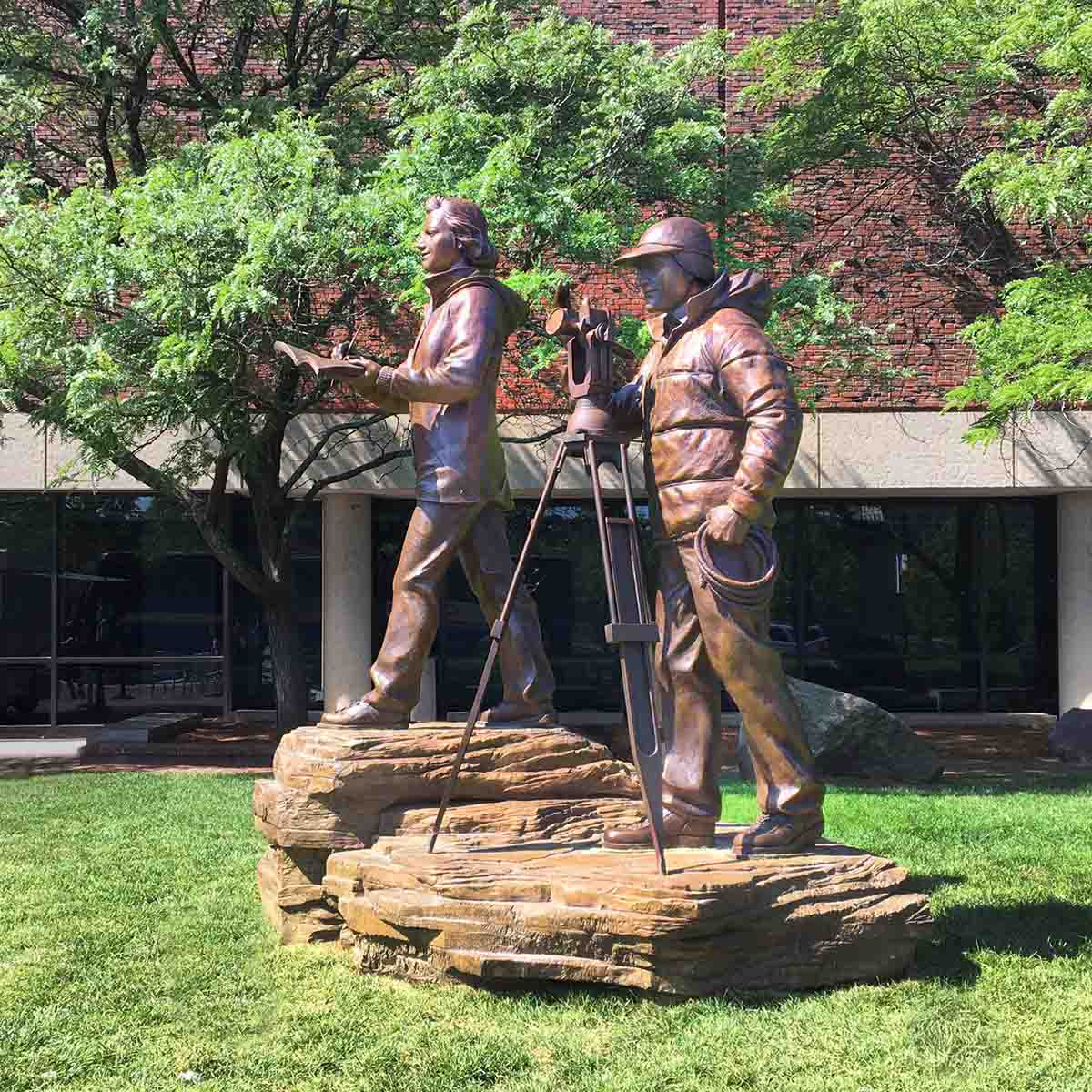 photo of bronze sculpture of man and woman in winter gear with theodolite on tripod and notepad standing on rock surface in front of a building on a green lawn