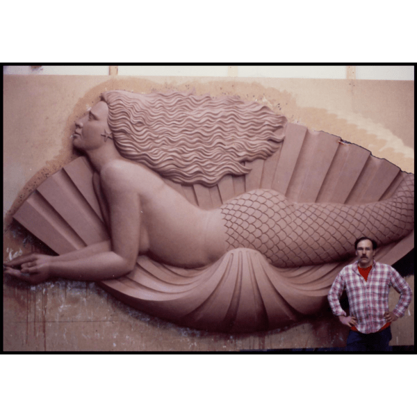 photo of clay model of sculpture of mermaid in profile laying on a shell on wood backing leaning against wall with sculptor Robert Shure standing in front
