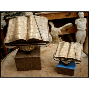 photo of two bronze-colored awards of sheet music open on a music stand with a conductor's wand, both atop pink marble bases