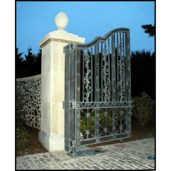 photo of one half of ornamental bronze entrance gate with stone pillars and shrubs to the side
