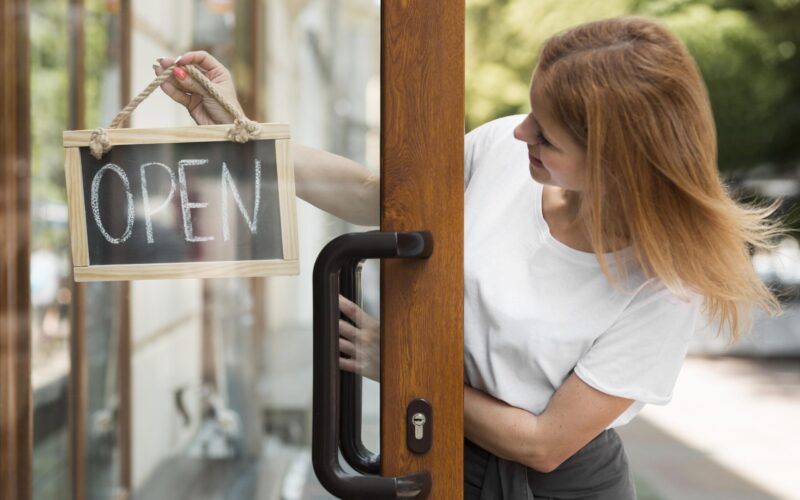 woman-holding-we-are-open-sign