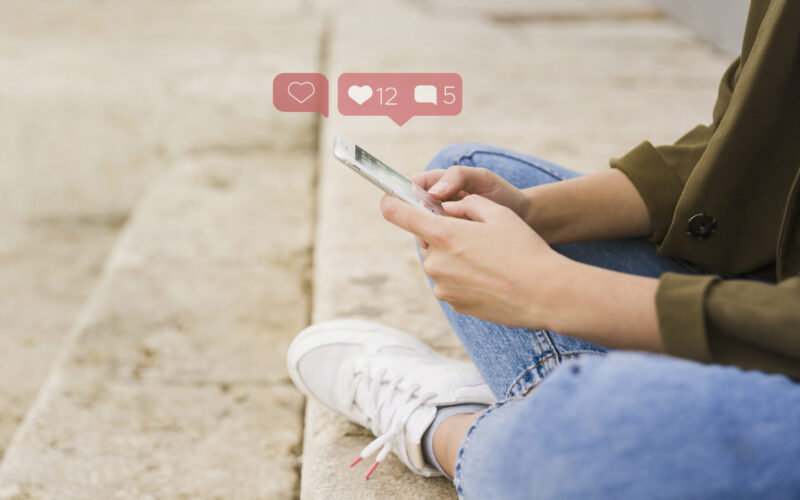close-up-woman-sitting-stairs-using-social-media-app-mobile
