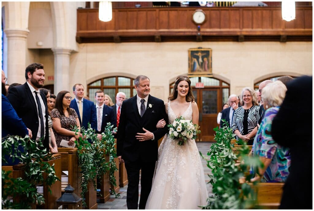 bride and father walk down aisle at ceremony at Holy Rosary Church in Houston Texas by Swish and Click Photography