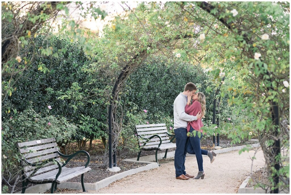 a couple kisses at their engagement photos at McGovern Centennial Gardens captured by Swish and Click Photography a Houston wedding photographer