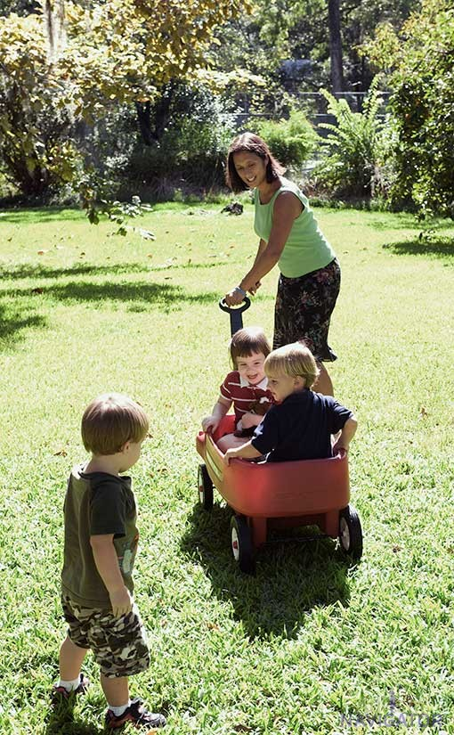 Mother pulling young children in wagon