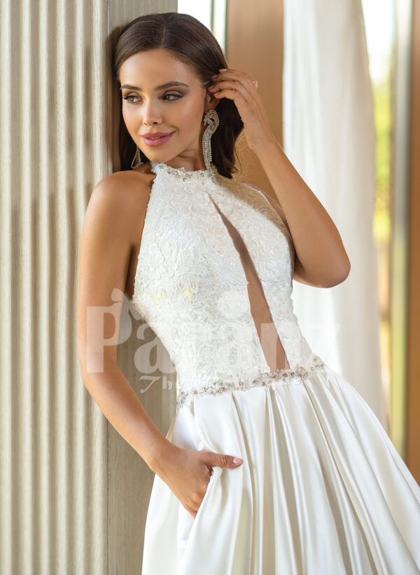 Closed neck and open back flared satin wedding gown with tulle skirt underneath close view