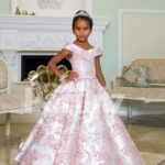 Criss-cross of shoulder style baby gown with flared and pleated high volume skirt