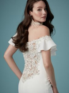 A sheath wedding gown with Chardon crepe, an illusion back with shimmering beaded floral lace motifs, an off-the shoulder neckline, soft ruffle sleeves accented with beaded floral lace motifs, crystal buttons, and a zipper closure.