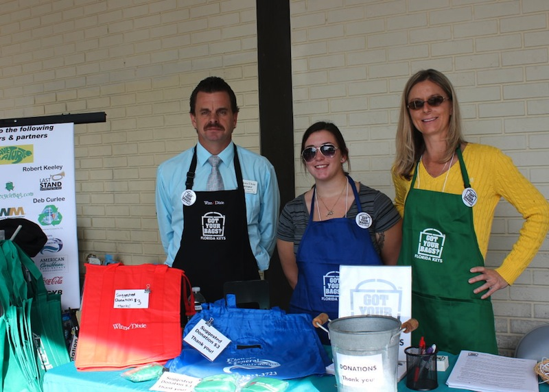 Kenny Lowe, Store Director for the Big Pine Key Winn-Dixie with Ashlee Fisher and Michele White, two of the volunteers at bag giveaway station outside Winn Dixie.