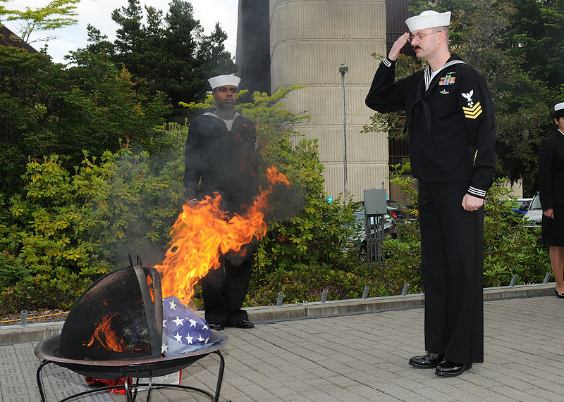 English: SILVERDALE, Wash. (June 14, 2010) Machinist's Mate 1st Class Scott T. Coykendall, an instructor at Trident Training Facility (TTF), salutes the burning remains of 14 national ensigns during a flag burning ceremony Naval Base Kitsap, Wash. Students and staff from TTF participated in the flag burning ceremony. (U.S. Navy photo by Mass Communication Specialist 2nd Class Chantel M. Clayton/Released) (Photo credit: Wikipedia)