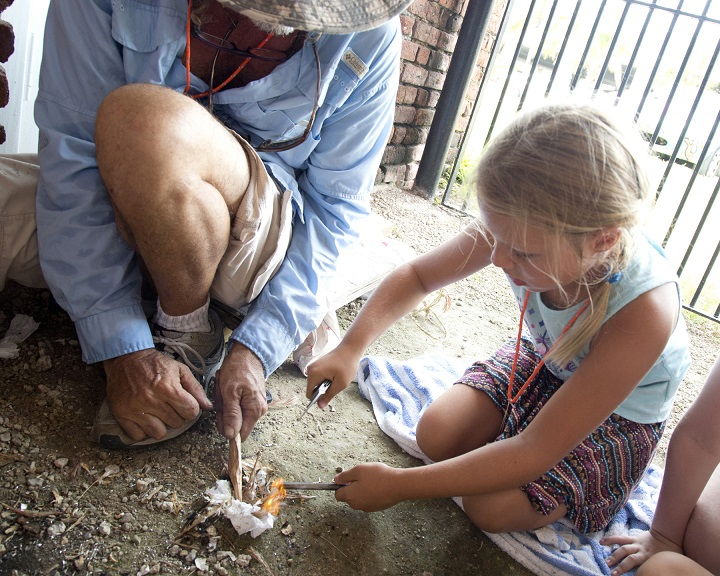 Key West Art & Historical Society ArtCamp! instructor Lee Starling (left) taught students  about the tools and responsibility of working with fire during his Native American Craftsman ArtCamp! last week. On Friday, Sierra Krames employed a knife, flint and ferro rod to spark a campfire.