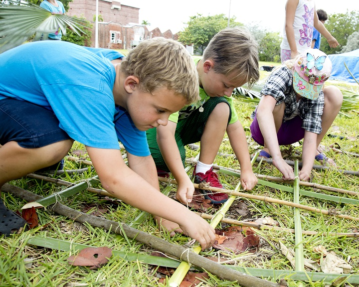 West Art & Historical Society Native American Craftsman ArtCamp! students (left to right) Joshua Johnson, Jakub Kolar and Maddison Bock lash palm fronts and branches together while learning to build a fort during ArtCamp! last week.