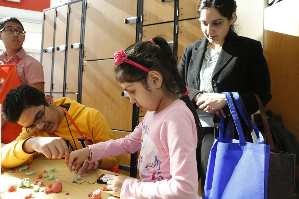 Virginia Run Elementary School student Bonnie Gill, 5, tries a science experiment with the help of Ishaan Lubana of the Children's Science Center while her mother Sheena Gill looks on.