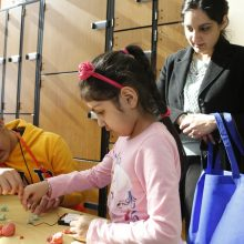 Virginia Run Elementary School student Bonnie Gill, 5, tries a science experiment with the help of Ishaan Lubana of the Children's Science Center while her mother Sheena Gill looks on, at the 2015 K-12 STEM Symposium