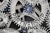Macro photo of tooth wheel mechanism with Partnership related words imprinted on metal surface