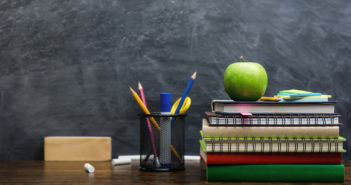 Books, stationery and education supplies on wooden desk in classroom with blackboard in background
