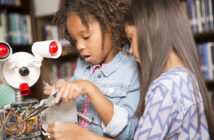 Elementary age African and Latin descent little girls work on building a robot in technology class in school classroom or library. STEM topics.
