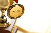 A gold medal hanging on a trophy with 2018 engraved on the medal. Trophy is sitting on soft golden satin that provides ample room for copy and 8 (A gold medal hanging on a trophy with 2018 engraved on the medal. Trophy is sitting on soft golden satin sheet