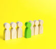 The green figure of a man comes out of the line of people on an yellow background. Talent, leader, professional. concept of success and improvement in work, the universal recognition of efficiency (The green figure of a man comes out of the line of pe