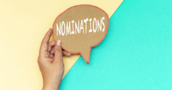 closeup hand holding nominations speech bubble