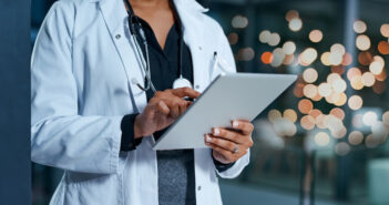 Closeup shot of an unrecognizable doctor using a digital tablet in a hospital at night