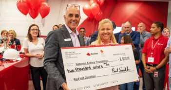 Paul Smith presents Michele Anthony a donation check at Red Hat's Open House (new office) on Sept. 12, 2019.