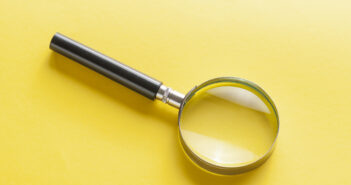 Magnifying glass lying diagonally on yellow