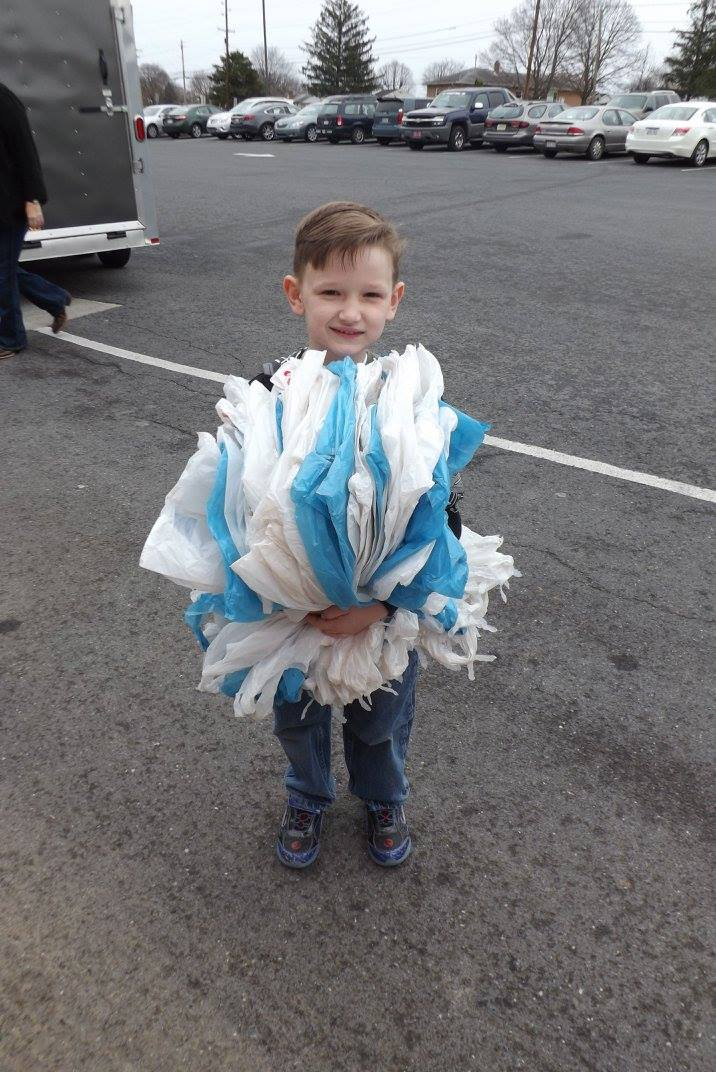 a little boy stands holding in both arms a huge stack of plastic grocery store bags, which are used to deliver food to children