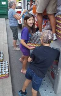 a little girl helps unpack boxes of soup cans from a truck