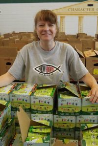 A woman smiles as she pauses from unpacking boxes of applesauce amid a large school cafeteria stacked with food boxes.