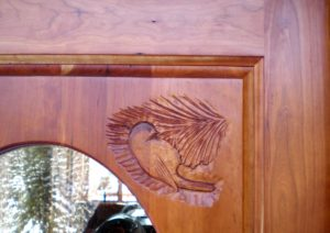Carving of a chickadee on a custom built cherry entry door