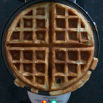 A just-finished round sourdough waffle on a waffle iron.