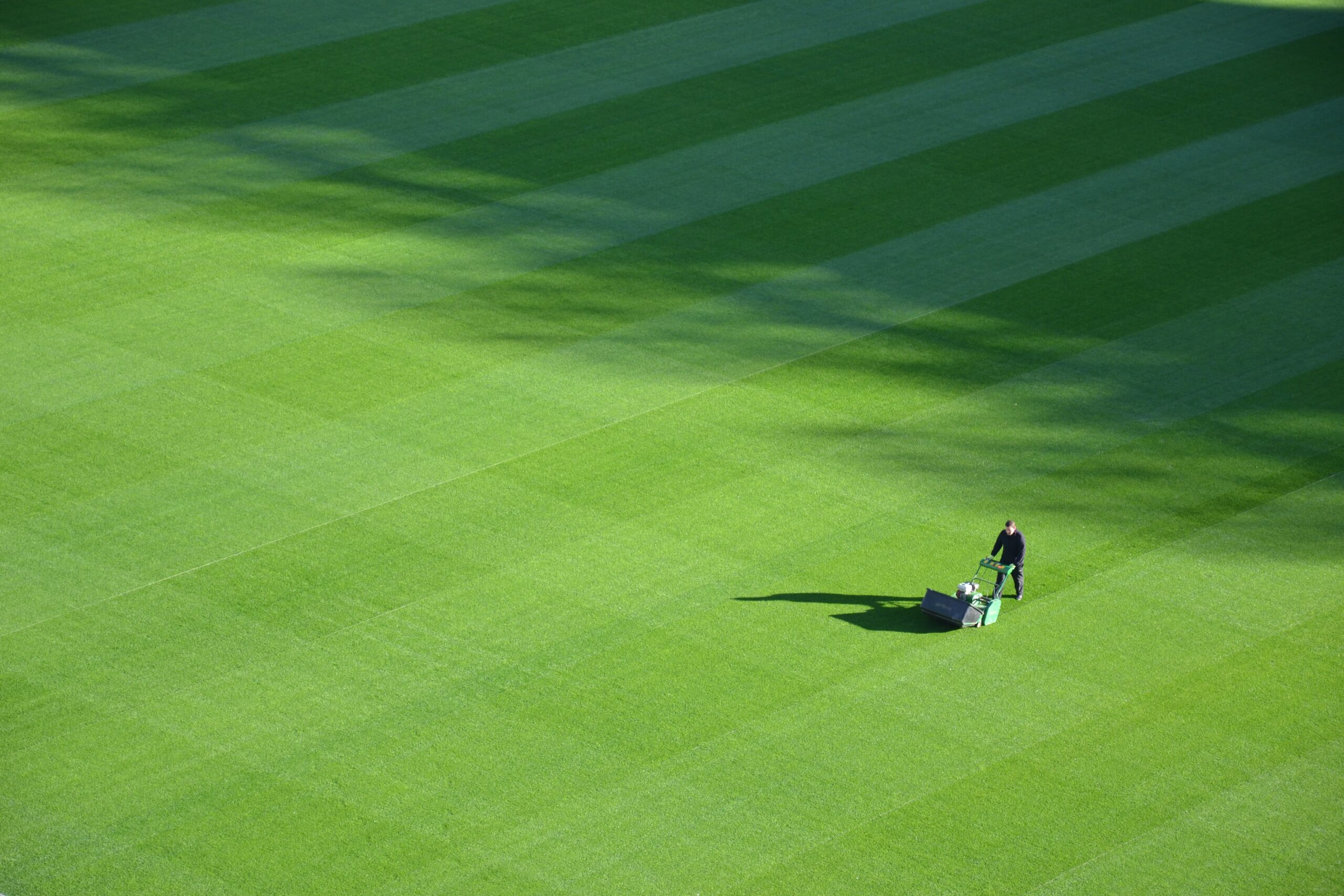 Landscaper mowing a flat, green lawn in a crisscross pattern